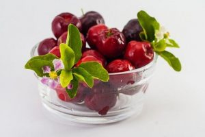 Acerola fruits in a ball with some leaves