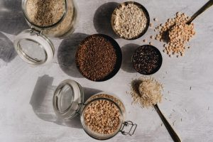 different cereals in glass jars and spoons