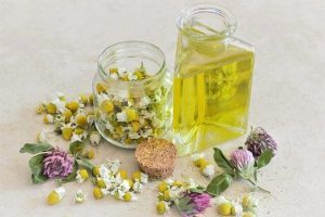 Chamomile essential oil with a jar full of chamomile petals