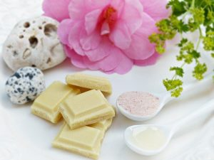 Pieces of white chocolate next to pink flower and spoons full of cocoa butter