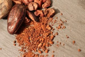 Cocoa beans next to powdered cocoa on a wooden surface