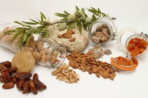 A bunch of different nuts and dried fruits spilled out of jars