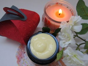 Organic cream next to a candle, white flowers and a red packaging