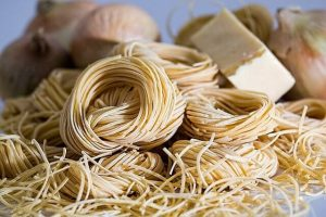 Dry pasta close up with out of focus onions and cheese