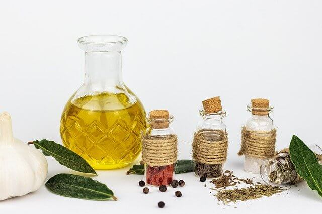 different bottles of herbs and essential oils with leaves