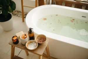 Relaxing bath with bath salts and cosmetics on a side table