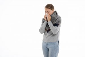 A woman with a cold blowing her nose and wearing heavy clothes