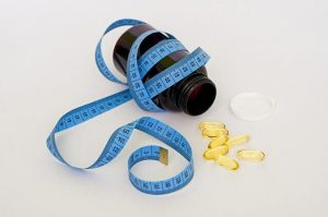 Pill bottle spilling yellow pills with a measuring tape wrapped around it