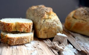 Fresh bread on a wooden board in a loaf and slices