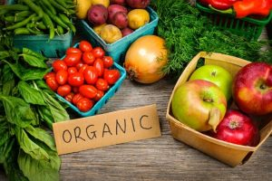 """fruits and vegetables with a piece of cardboard with """"Organic' written on it"""