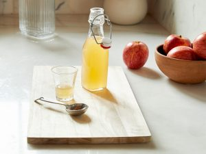 wooden board with apple cider vinegar, apples and a spoon on it