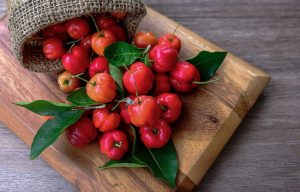 Wooden board with acerola fruits on it