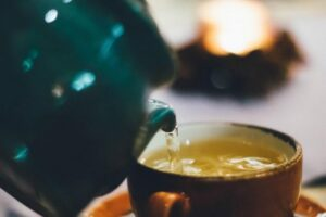 photograph of a teapot pouring tea into a teacup and background out of focus