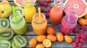 Vitamin c fruits in colors and juices in the middle