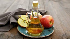 plate with apples and a bottle of apple cider vinegar