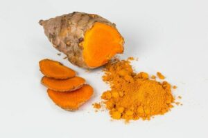 Turmeric plant with slices and powder in orange color